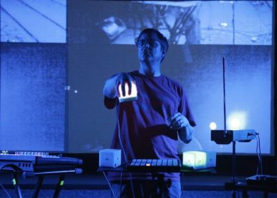 """Playing the song """"I Can See Them"""" live. I'm controlling 4 dimensions of at the same time. Visuals behind me are by artists Project Ruori who are processing a live camera feed. Photo by Hong Waltzer."""